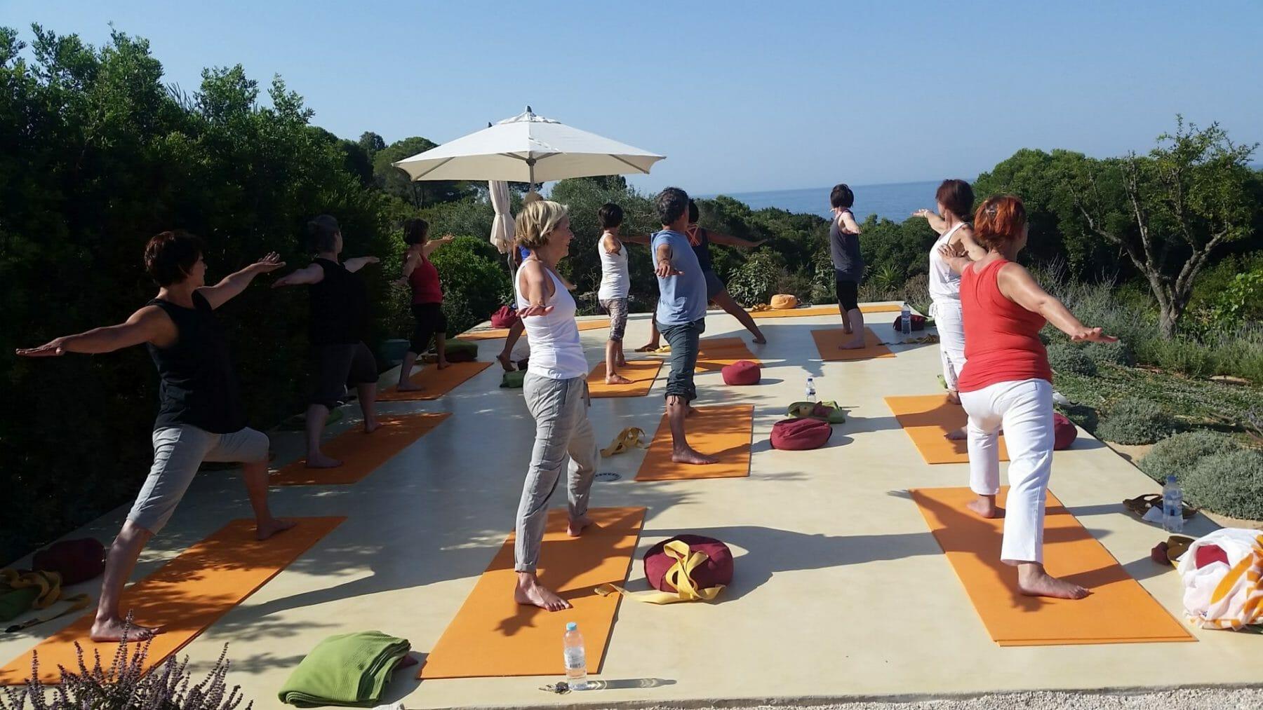 Gruppe auf Yogaplattform im Sommer Yoga Retreat mit Blick aufs Meer