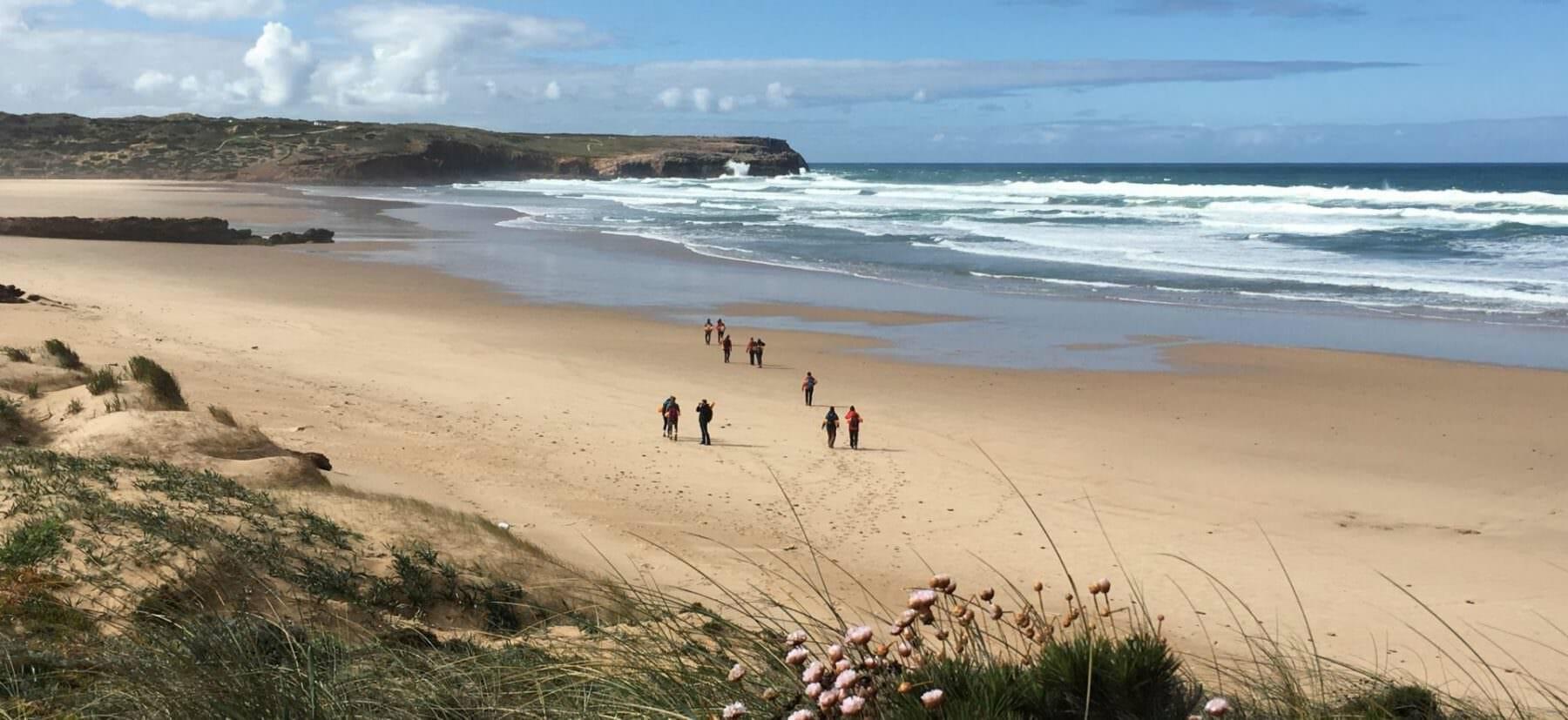 Wandergruppe auf weitem Sandstrand an der Algarve Westküste