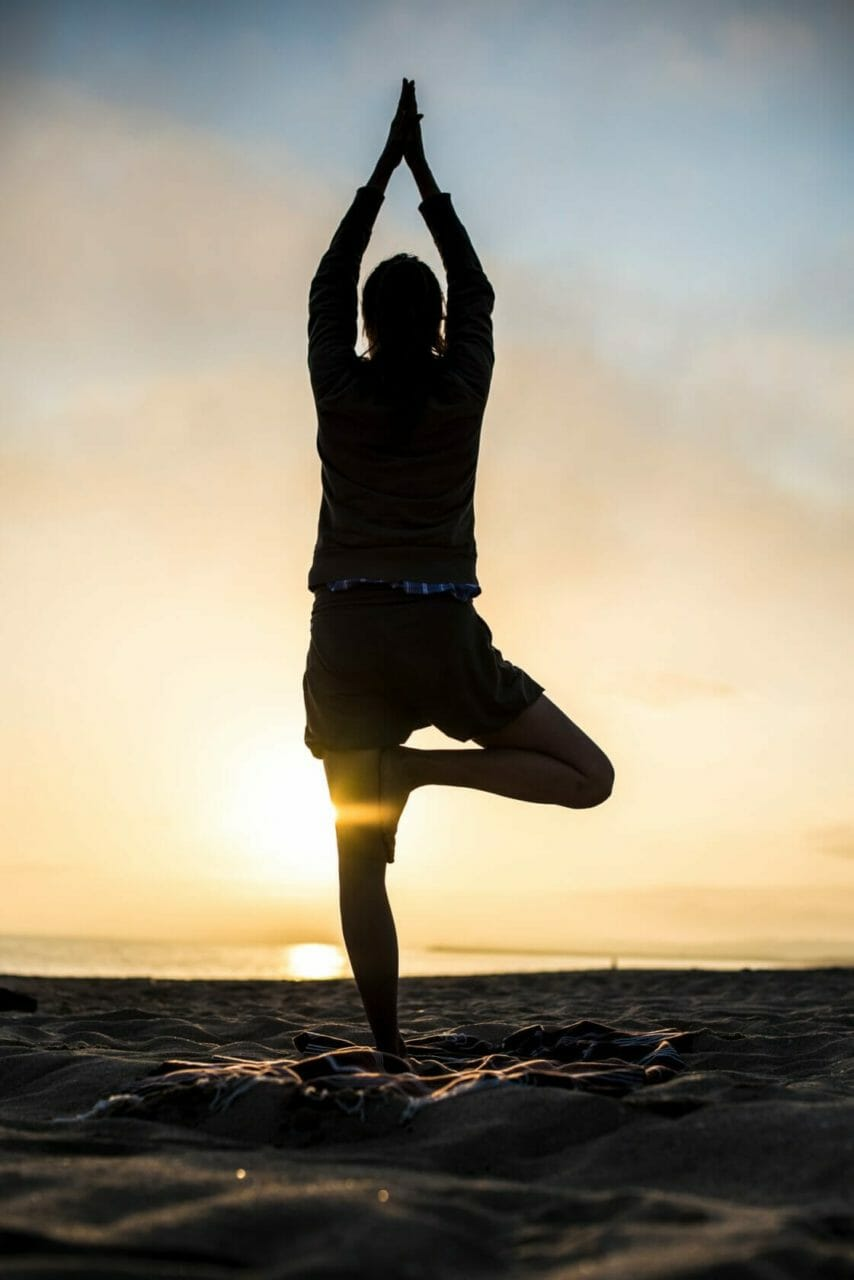 Yoga Asana Baum am Algarve Strand im Gegenlicht