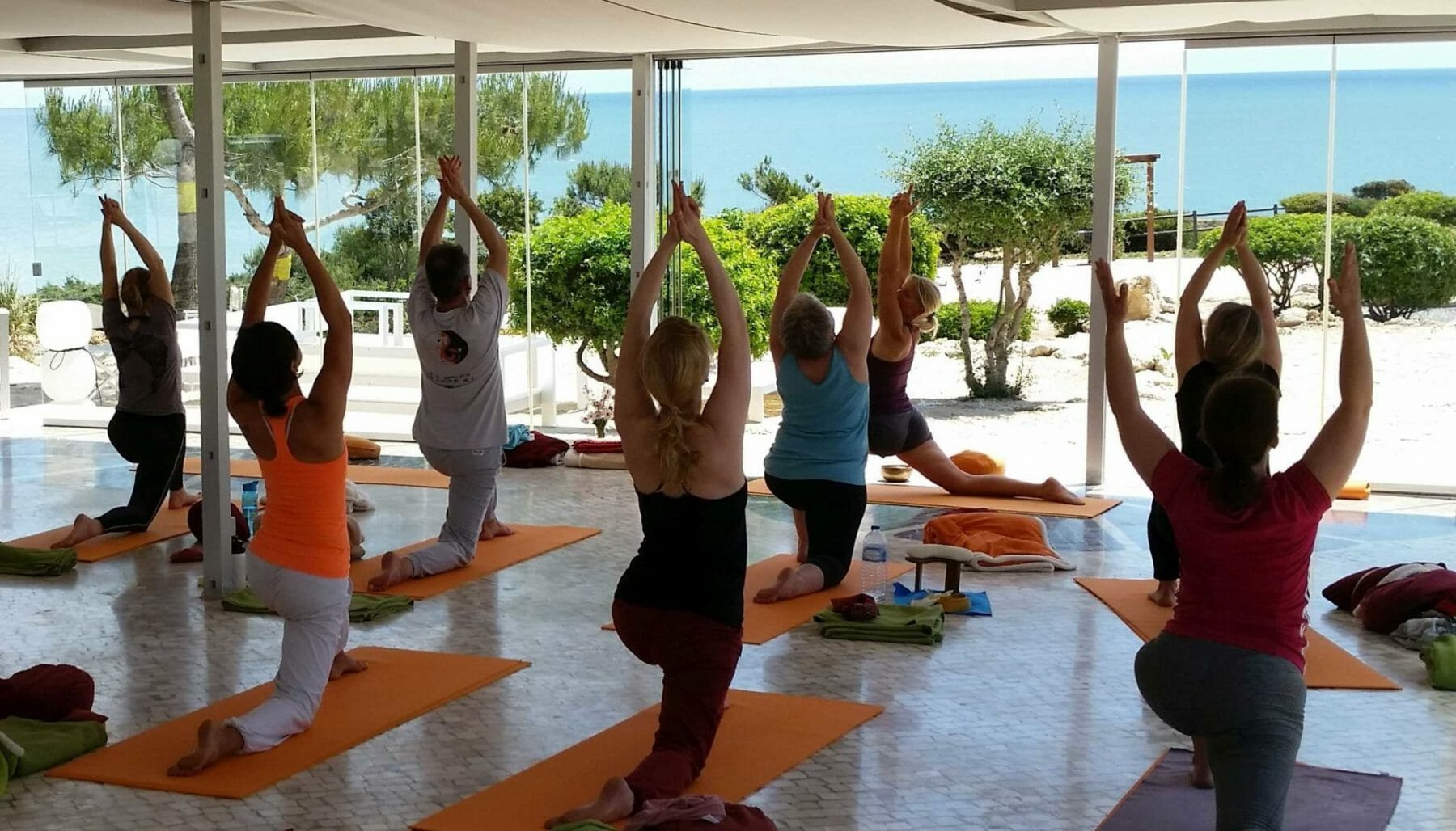 Yogagruppe am Meer auf Klippe über dem Atlantik