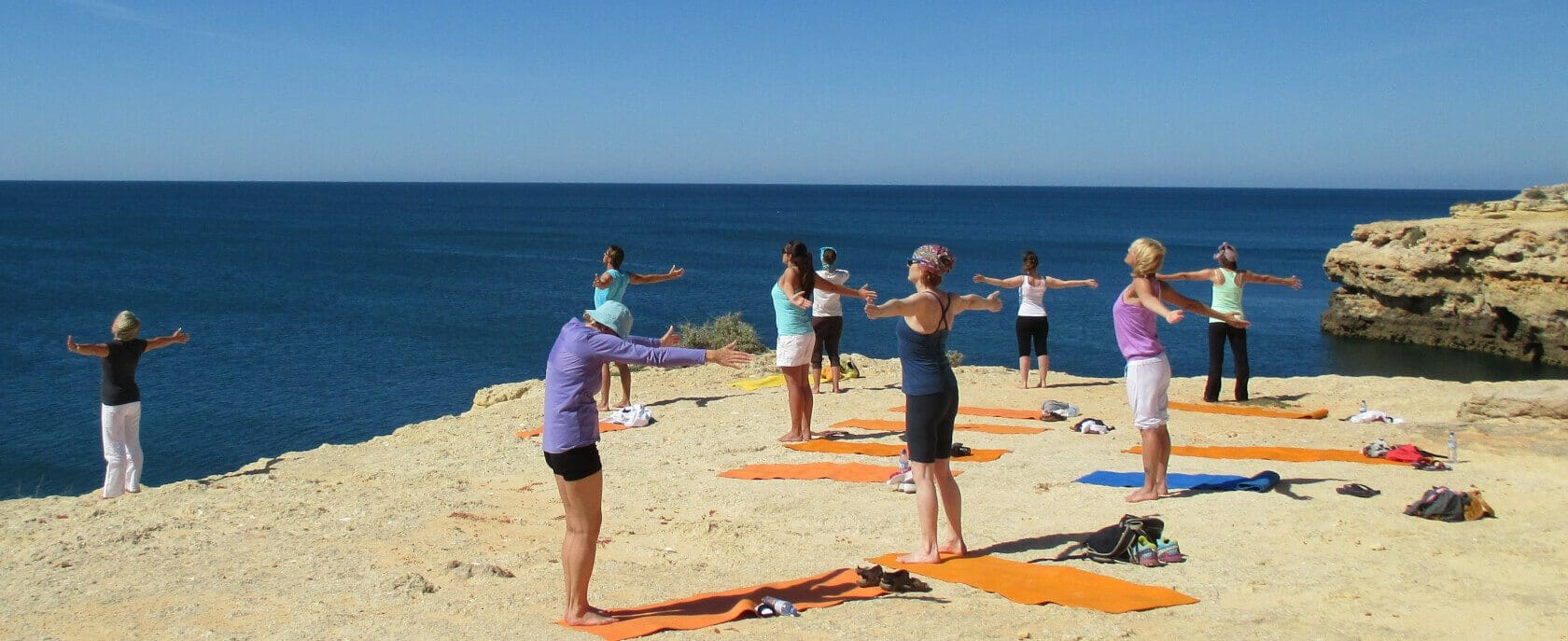 Qi Gong Urlaub: Gruppe übt auuf Klippe am Meer