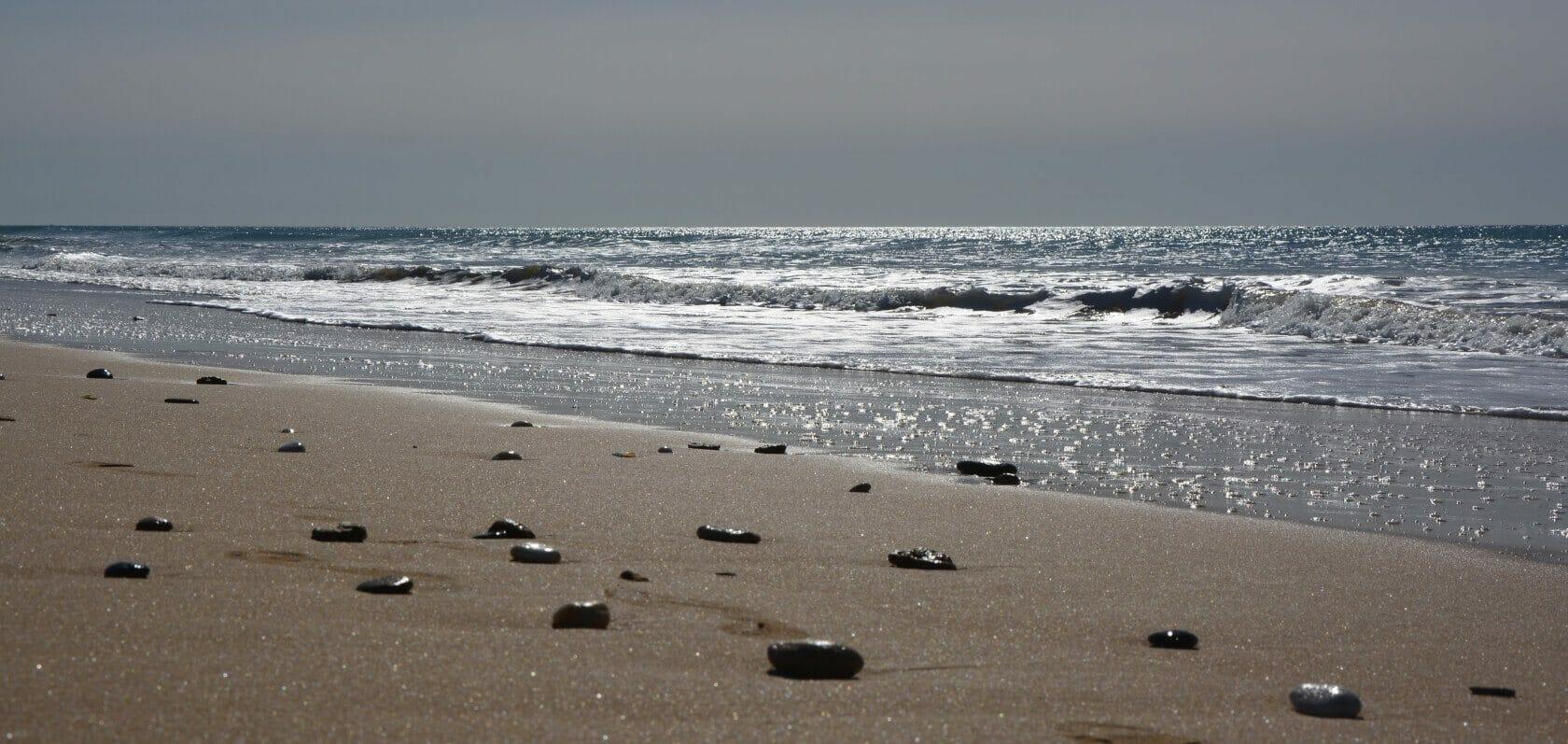 Steine auf Sandstrand am Meer